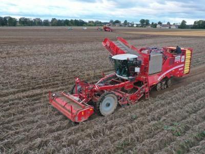 czerwony kombajn zbierający uprawy z pola