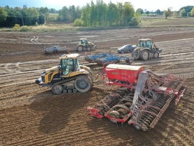 trzy traktory na polu uprawnym